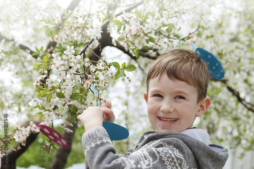 Happy boy among blooming garden