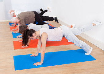 Trainer And Customers Doing Exercises