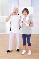 Senior Couple Taking Break After Workout At Gym