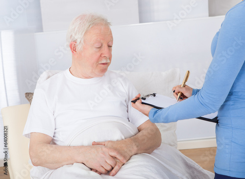 Caretaker With Clipboard Attending Senior Patient