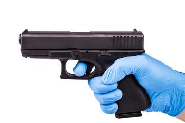 Hand in blue latex glove aiming with handgun