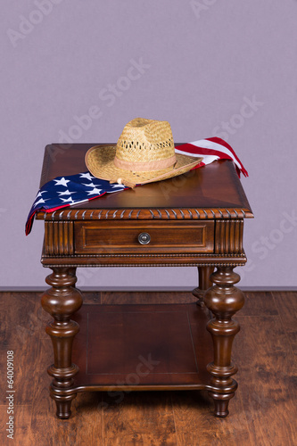 Wooden table with hat and american flag on hardwood floor