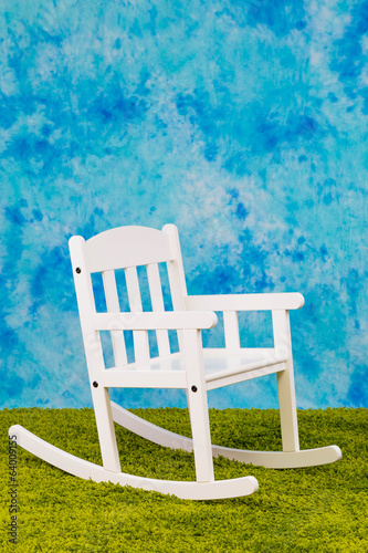 White child's chair on sky and grass backround