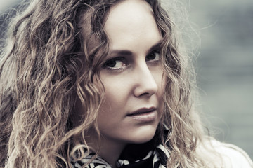 Sad beautiful woman with long curly hairs