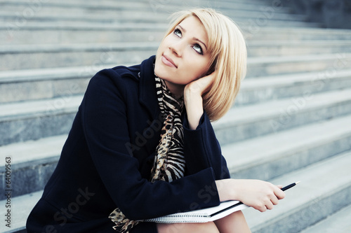 Young business woman with notebook sitting on the steps