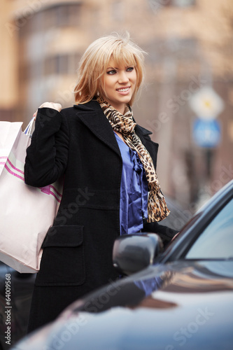 Young woman with shopping bags at the car