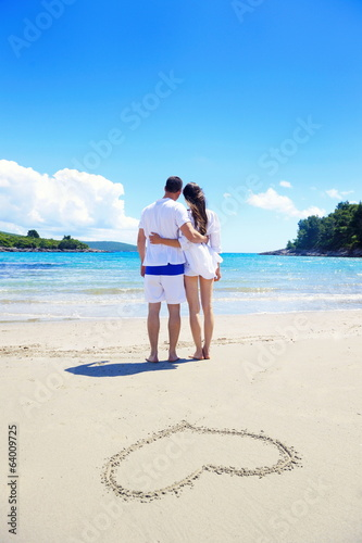 romantic  couple in love  have fun on the beach with heart drawi