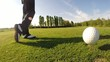 Golfer performs a golf shot from the tee. Sunny summer day.