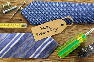 Happy Fathers Day tag with ties and tools on a wood background