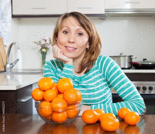 Smiling  housewife with mandarins