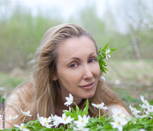 young beautiful woman on glade of blossoming snowdrops