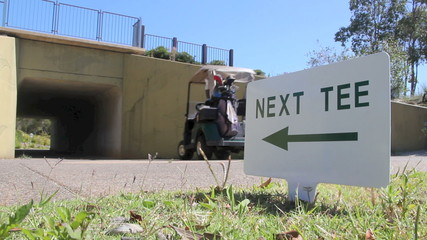 Golf buggy driven by a next tee sign going into a tunnel.