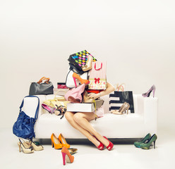 Attractive girl with heap of shoes