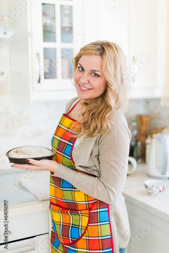 Woman pulling pie from oven