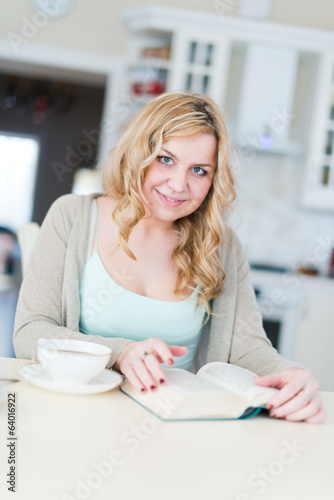 woman drinking coffee and reading book
