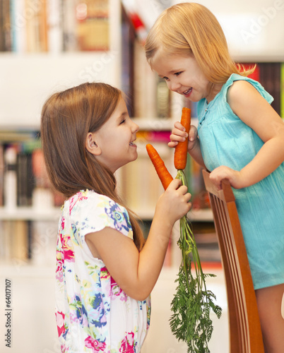 Little smiling girls with carrots