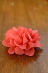 Coral flower brooch on brown table