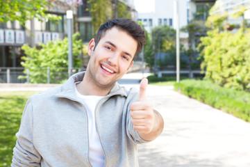 Lachender junger Mann mit Weste zeigt den Daumen