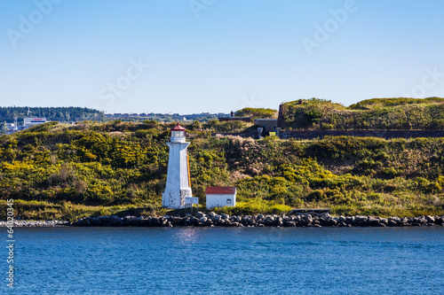 White Lighthouse on Green Grassy Coast