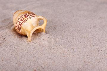 Greek ceramic amphora on sand, close up