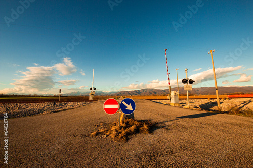 railroad crossing with mountains behind