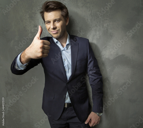 Man in suit showing the OK gesture