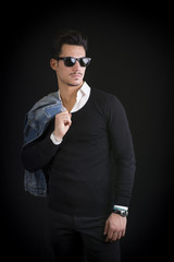 Attractive, trendy young man with black sweater and sunglasses