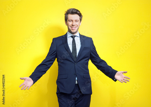 Friendly young businessman in open pose