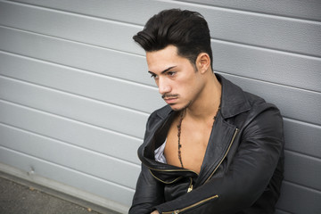 Young man with leather jacket sitting on the ground