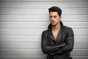 Young man with black leather jacket, arms crossed