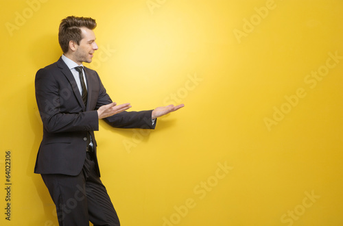 Handsome brunette businessman indicates something