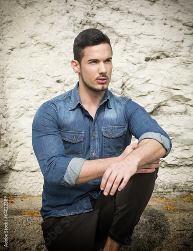 Handsome young man sitting outdoors in front of stone