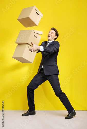 Cheerful businessman with paper boxes