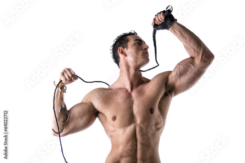 Muscular shirtless young man with handcuffs, whip and glove