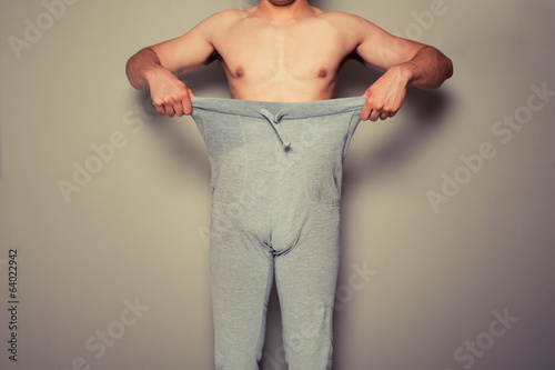 Young man pulling at his trousers