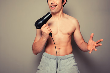 Athletic young man with a hair dryer