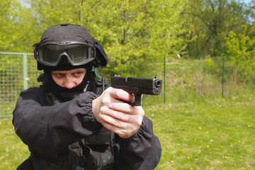 officer in tactical helmet pointing a gun