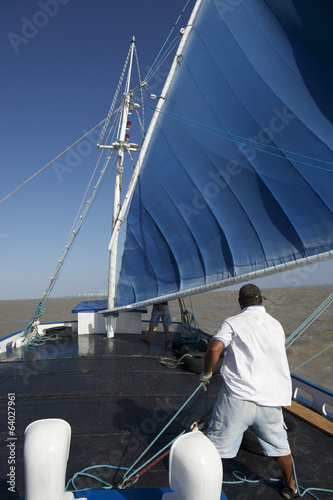 Brazilian Sailboat with Blue Sails in Turbulent Waters