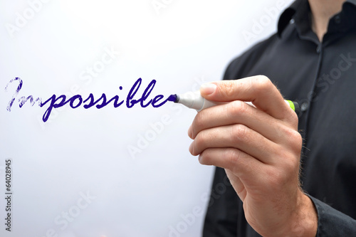 Man writing a the word impossible with a marker