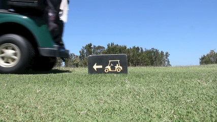 A golf buggy is driven by a golf buggy sign.