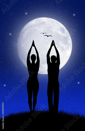 couple doing yoga in the moonlight