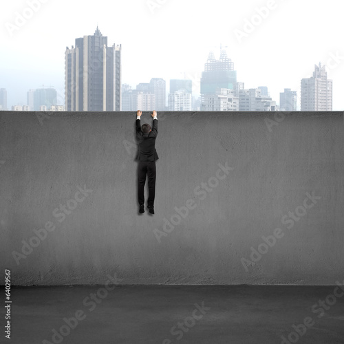 Businessman trying to cross over wall with city view