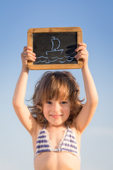 Happy child holding blank blackboard