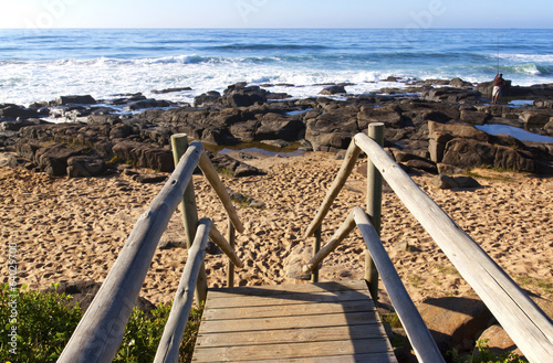 Weathered Wooden Stairway Leading onto Rocky Beach