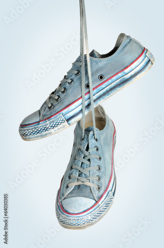 Pair of blue sneakers hangs on the laces