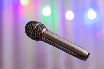 The microphone on the background of multicolored light bulbs