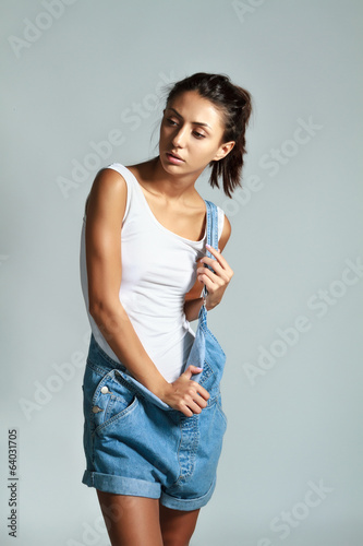 Young female in denim overalls isolated on gray