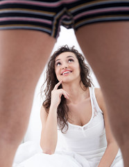 young woman looking under man leg