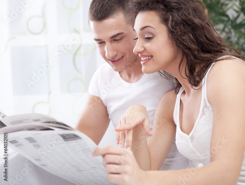 A young couple in bed reading a newspaper