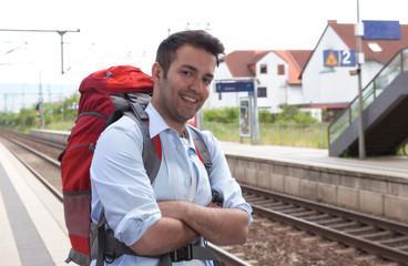 Lachender Rucksach-Tourist wartet am Bahnhof
